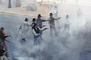 Actors dressed as cowboys reenact a gun fight in the streets of Cody