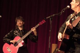 A woman plays acoustic bass guitar as a man sings and plays acoustic guitar