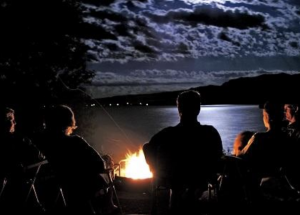 Friends sit around a fire in the evening