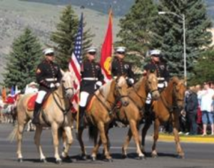 Four service members ride horses while carrying flags in a parade