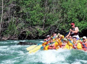 A group of tourists paddle through rapids on the Shoshone  River