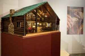 A wooden dollhouse on display at By Western Hands Gallery and Museum